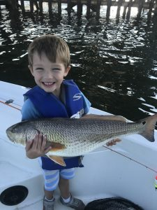 toddler holding fish as big as he