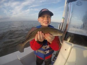 Smiling boy holding speckled trout