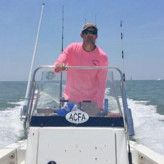 man wearing pink shirt driving boat