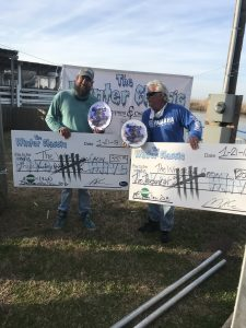 two fisherman holding big checks and plaques