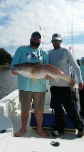 two men holding trophy sized bull redfish