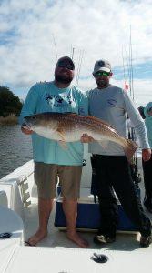 two men holding trophy sized bull redfish