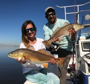 man and woman each holding redfish