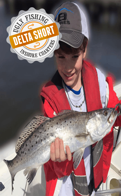 boy holding speckled trout on mobile delta