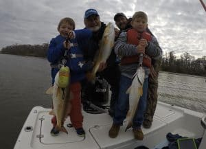 two men two boys holding 3 redfish