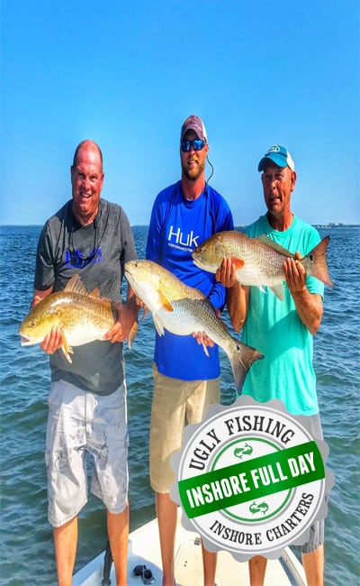 Men holding redfish on boat in Mobile Bay