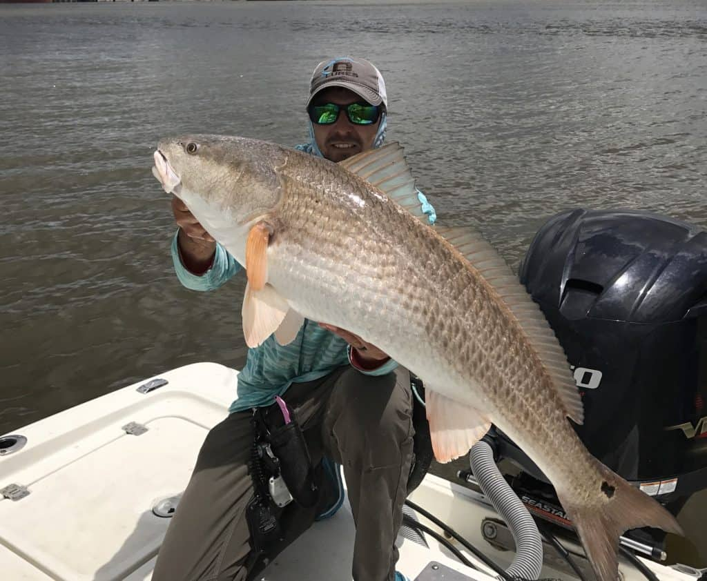 man holding big bull redfish