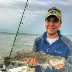 man holding speckled trout