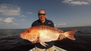 man holding red snapper