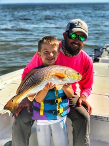 Man and boy holding redfish