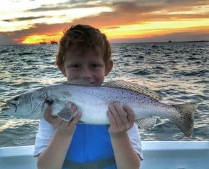 child holding big speckled trout