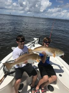 two boys each holding large redfish
