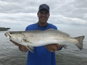 man holding trophy sized speckled trout