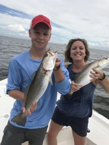 mom and son each holding speckled trout
