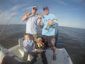 family holding speckled trout