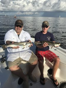 two men each holding big speckled trout