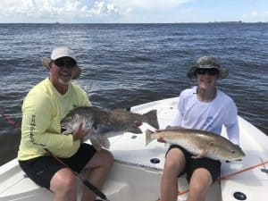 man and boy each holding big fish