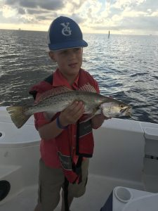 boy holding speckled trout