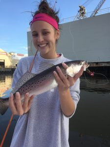 young lady holding speckled trout