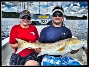 man and woman holding big redfish