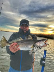 man excited holding big speckled trout