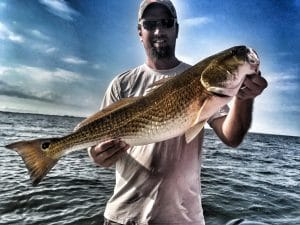 Man-holding-Alabama-bull-redfish-on-boat