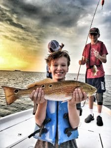 teenager-smiling-holding-slot-redfish