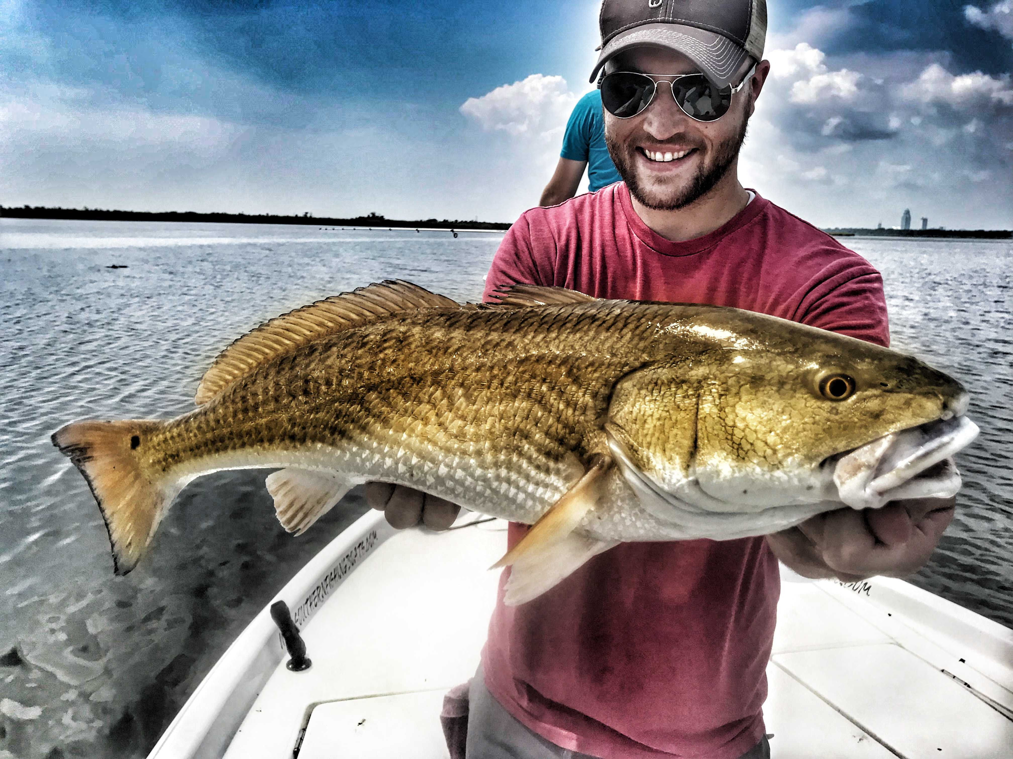 man-smiling-holding-big-redfish-while-standing-in-boat