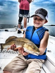 child-wearing-life-jacket-sitting-on-a-boat-holding-redfish