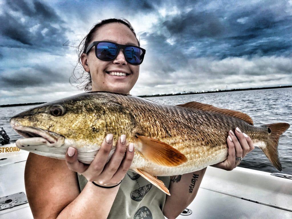 young-lady-holding-large-redfish