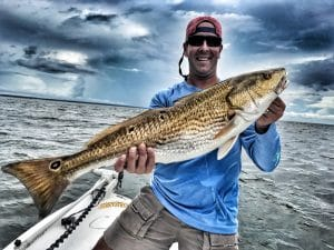 Man-holding-bull-redfish-while-on-boat