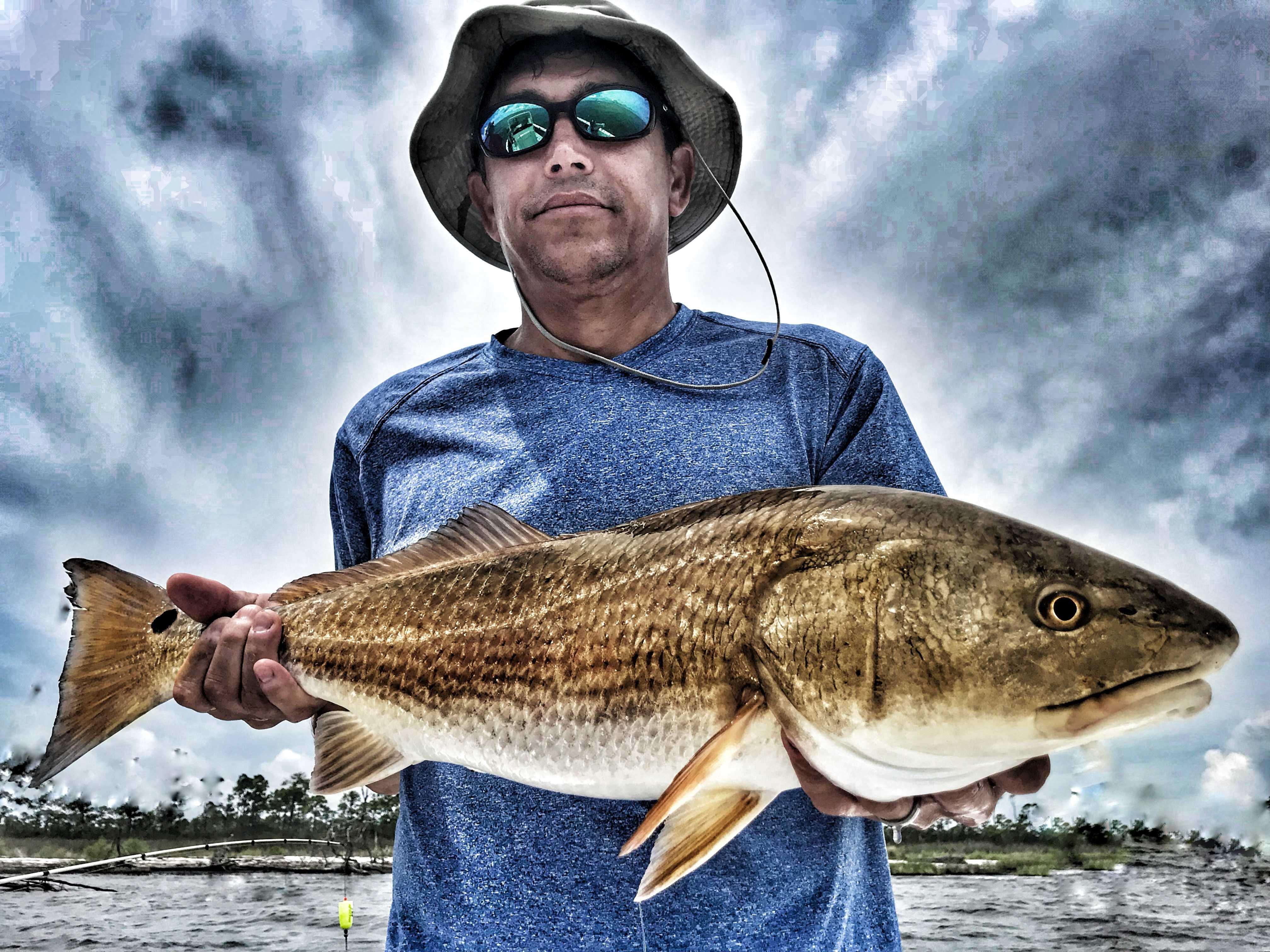 Man-holding-bull-redfish