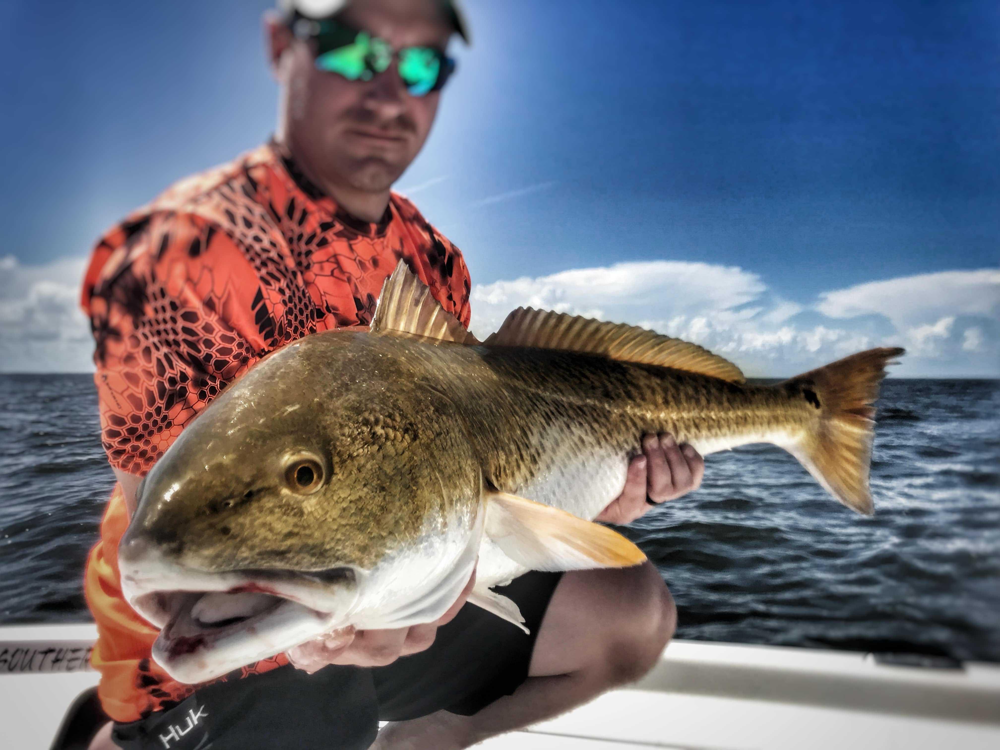man-holding-big-bull-redfish