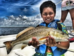 child-holding-redfish-on-boat