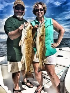 couple-each-holding-redfish