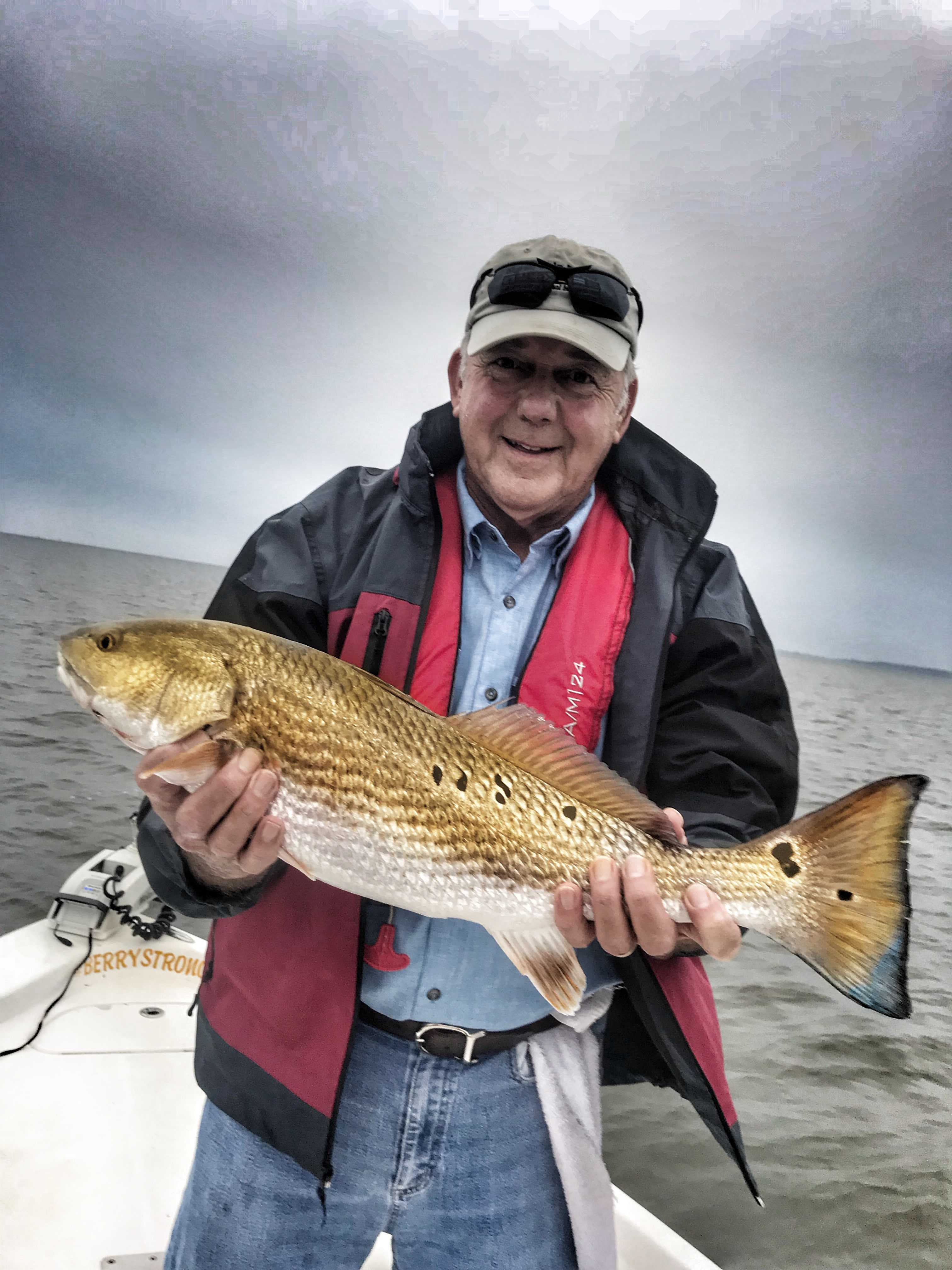 man-holding-redfish-while-fishing-with-captain-patric-garmeson