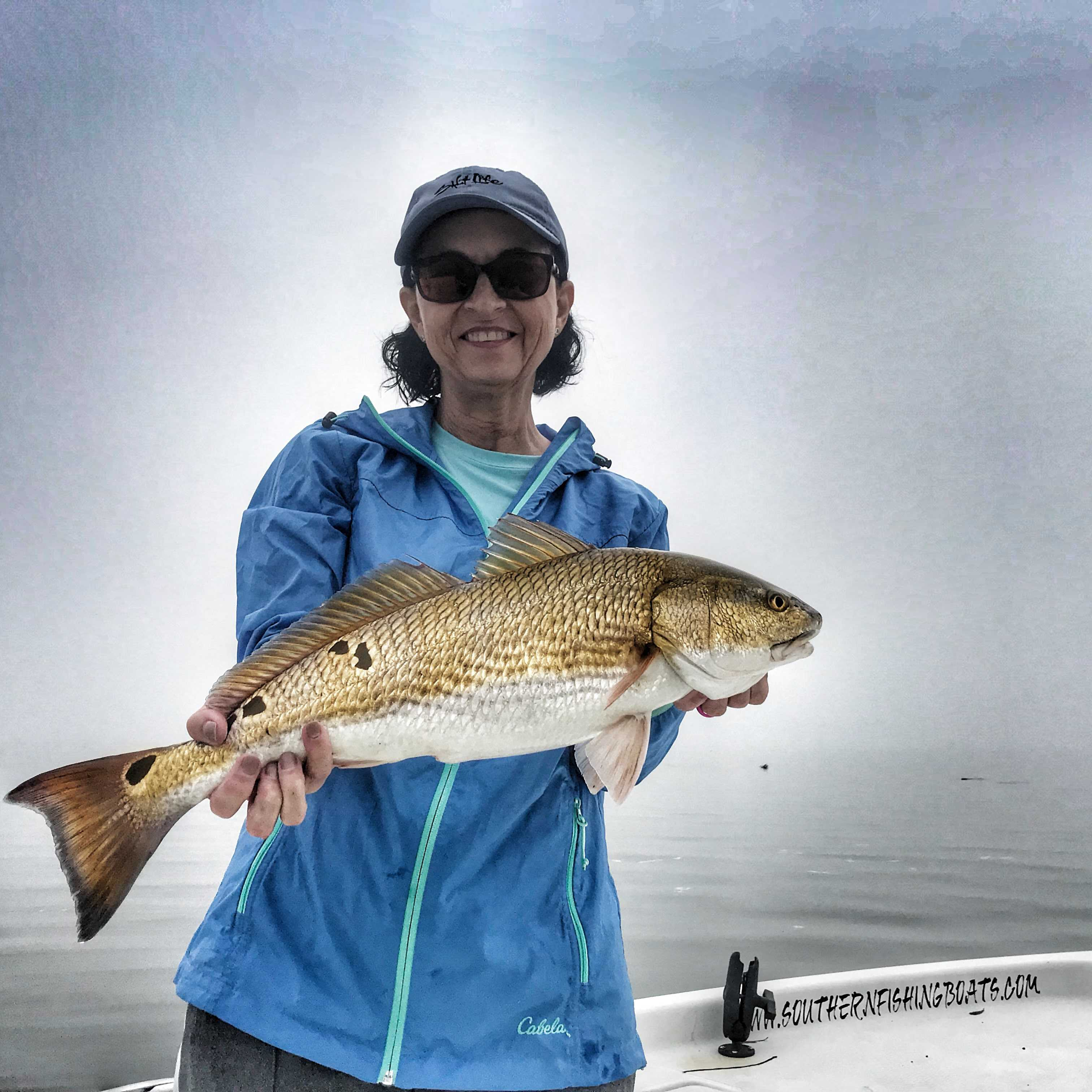 woman-holding-redfish-on-blue-wave-boat