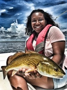 girl-holding-redfish-wearing-life-jacket-on-boat