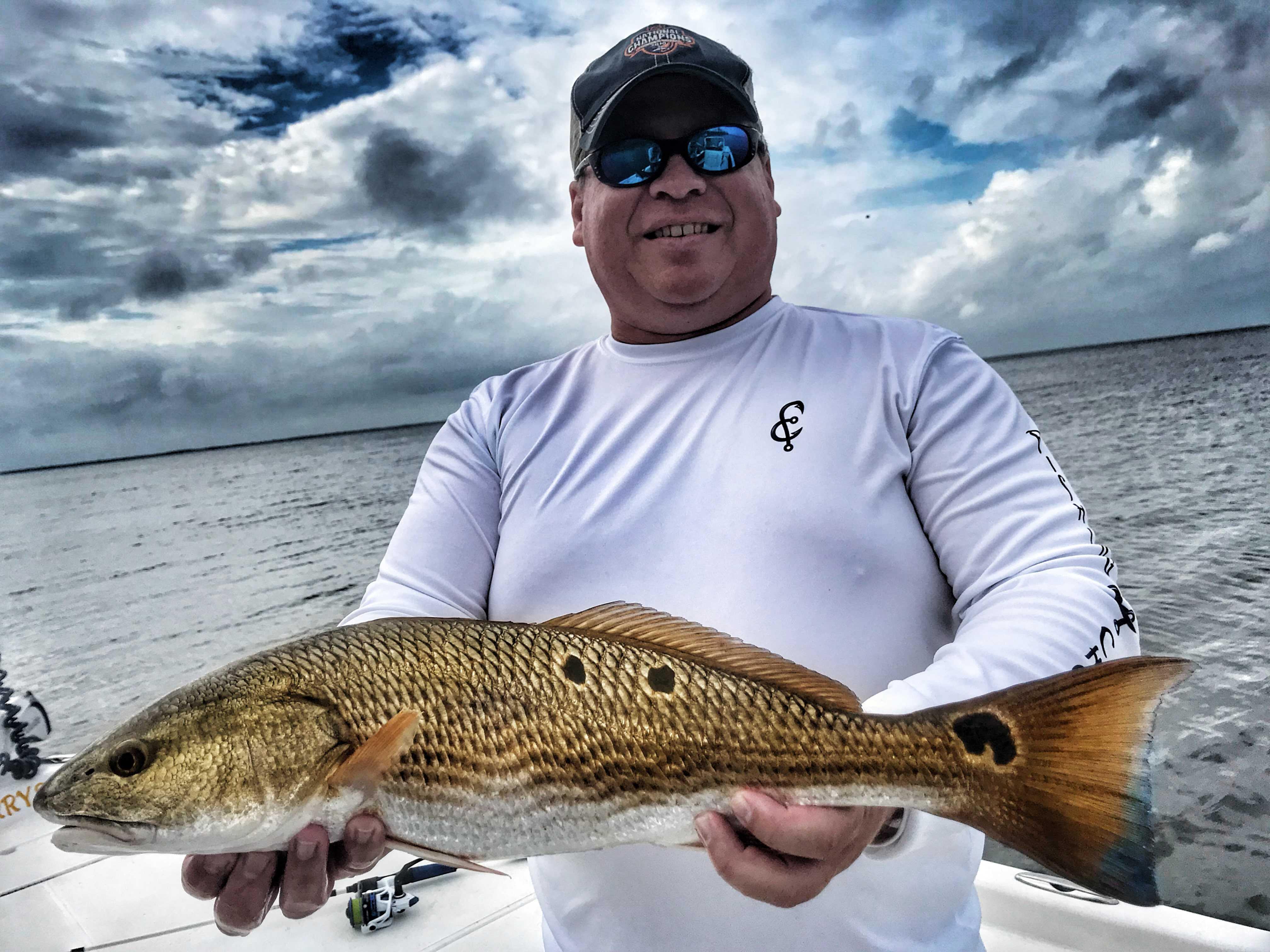 Man-wearing-fishing-chaos-shirt-holding-redfish