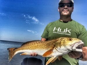 man-holding-slot-redfish