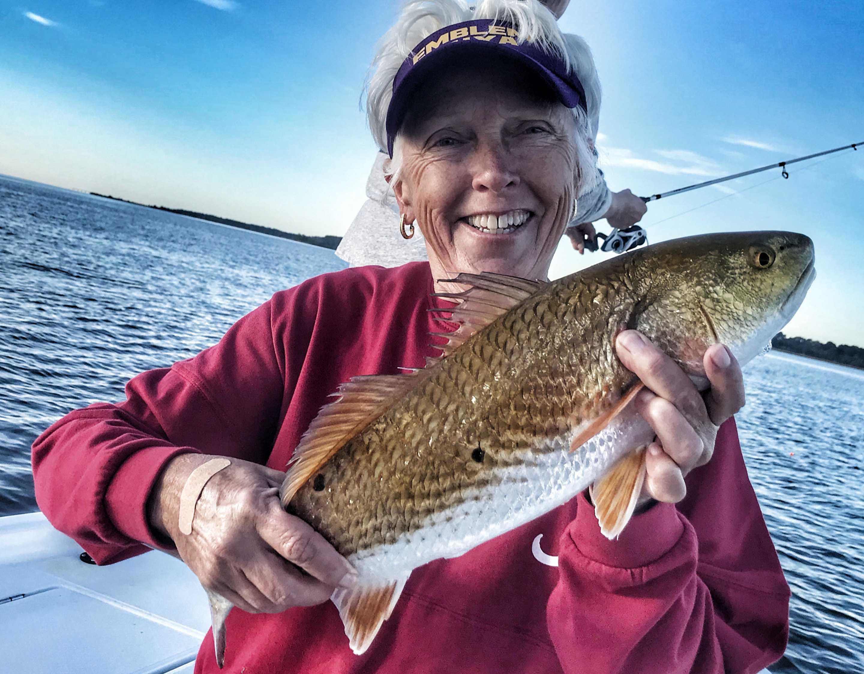 lady-holding-redfish-fishing-with-captain-patric-garmeson