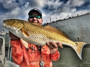 man-holding-redfish-with-question-mark-spot-on-tail