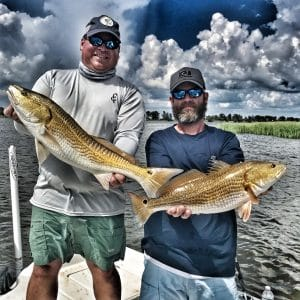 two-men-each-holding-slot-redfish