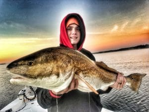 teenager-boy-holding-bull-redfish-before-sunrise