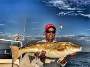 man-holding-two-spotted-bull-redfish