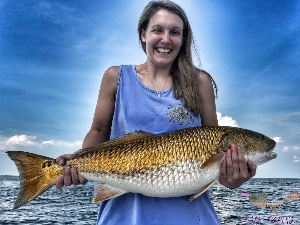 Dauphin island fishing charter lady holding large redfish