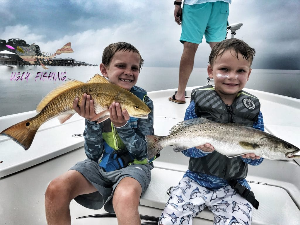 Mobile Alabama fishing charter two kids holding fish